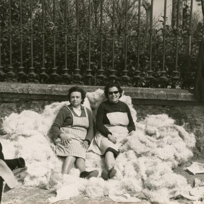 Mercè Pagés i Rosa Cendre al passeig Picasso, assegudes sobre un munt de palla