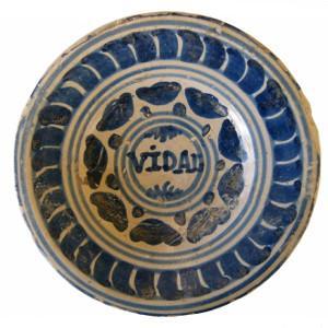 Detall d'un plat de ceràmica blava catalana decorada amb el motiu de la ditada.